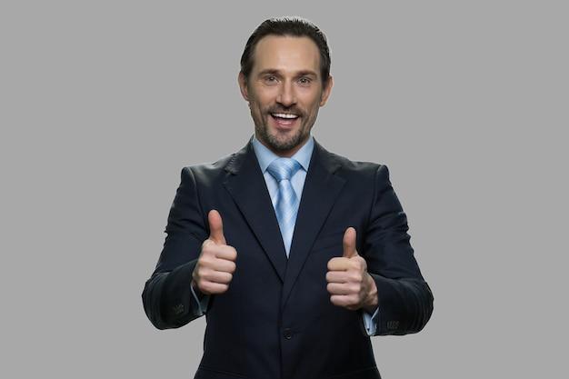 Erfolgreicher geschäftsmann, der daumen mit beiden händen aufgibt. porträt der fröhlichen männlichen exekutive auf grauem hintergrund.