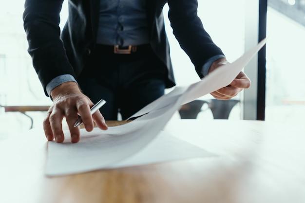 Erfolgreicher geschäftsmann, der dokumente in einem modernen büro signiert
