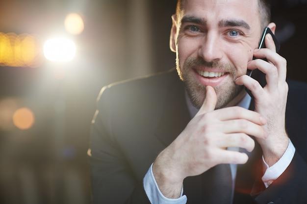 Erfolgreicher geschäftsmann, der durch smartphone benennt