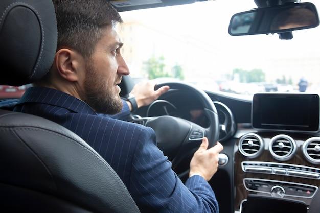 Erfolgreicher geschäftsmann, der ein teures auto fährt
