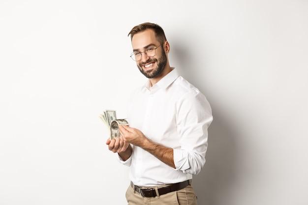 Erfolgreicher geschäftsmann, der geld zählt und lächelt, gegen weißen hintergrund steht und zufrieden schaut.