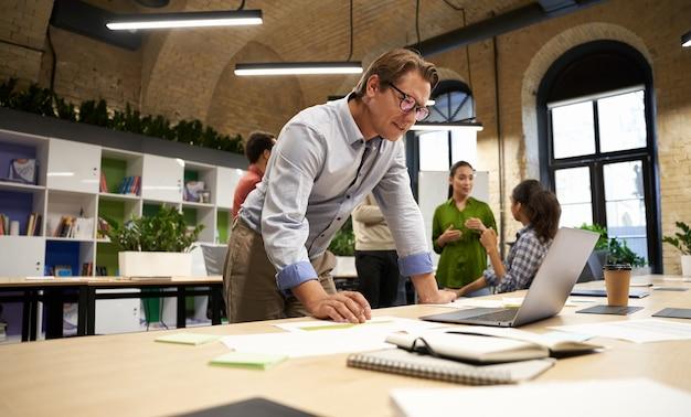 Erfolgreicher geschäftsmann, der im modernen coworking space steht und auf den laptop-bildschirm schaut und denkt
