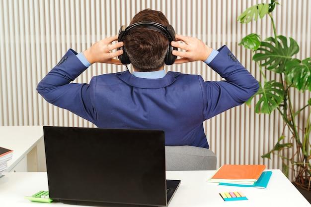 Erfolgreicher geschäftsmann, der in seinem büro stillsteht. geschäftsmann beendete großes projekt. büroangestellter in der rückansicht hören während der pause musik. junge männliche ruhe im stuhl von der computerarbeit abgelenkt.