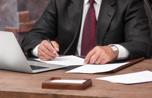 Erfolgreicher geschäftsmann, der mit dokumenten im büro arbeitet, nahaufnahme