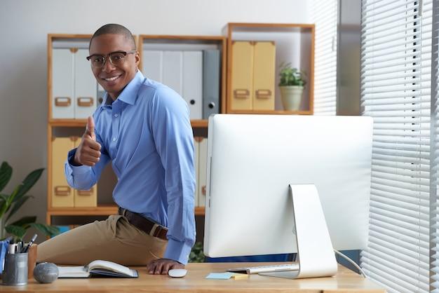 Erfolgreicher geschäftsmann, der sich daumen zeigt und auf seinem arbeitsschreibtisch hockend lächelt