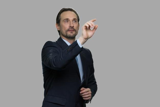 Erfolgreicher geschäftsmann, der virtuellen bildschirm berührt. hübscher männlicher ceo unter verwendung des transparenten virtuellen bildschirms. geschäfts- und zukunftstechnologiekonzept.