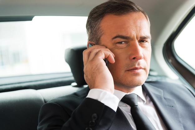 Erfolgreicher geschäftsmann im auto. selbstbewusster reifer geschäftsmann, der mit dem handy spricht und wegschaut, während er auf dem rücksitz eines autos sitzt