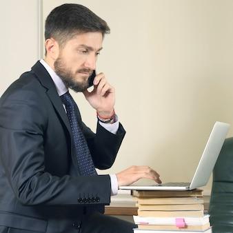 Erfolgreicher geschäftsmann im büro, der mit laptop arbeitet