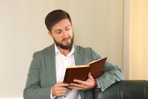 Erfolgreicher geschäftsmann im büro studiert das tagebuch
