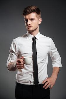 Erfolgreicher geschäftsmann in der abendgarderobe, die tasse kaffee im stehen hält