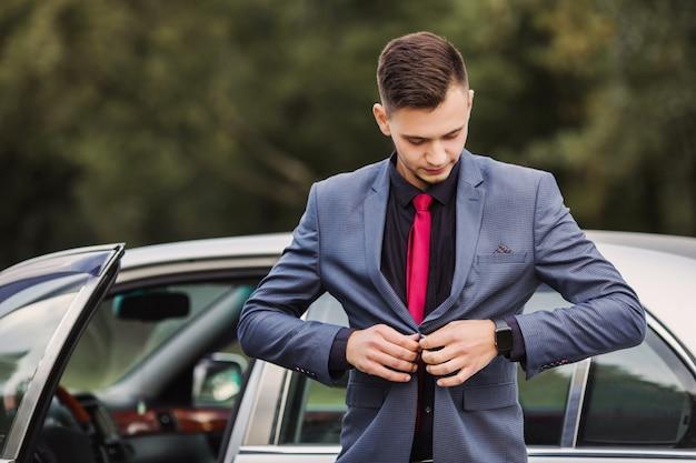 Erfolgreicher geschäftsmann in einem dunklen geschäftsanzug mit einer roten krawatte vor dem hintergrund eines autos. stilvoller mann. modische uhr zur hand. knöpfen sie einen knopf an der jacke zu
