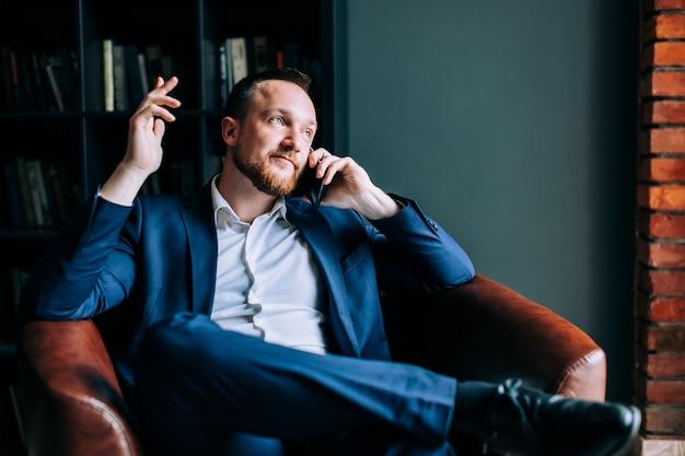 Erfolgreicher geschäftsmann in einer klage sitzt auf einem stuhl eines modischen büros und bespricht einen unternehmensplan auf einem smartphone.