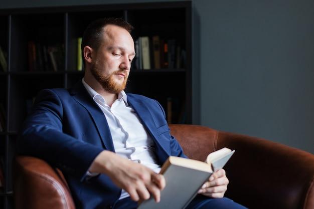 Erfolgreicher geschäftsmann in einer klage sitzt, ein buch lesend.