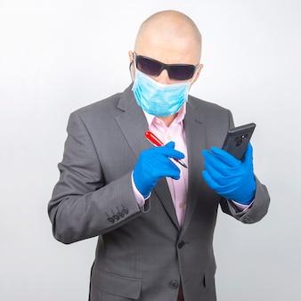 Erfolgreicher geschäftsmann in einer schutzmaske und handschuhen arbeitet auf einem smartphone während der quarantäne des coronavirus. freiberufler online arbeiten.
