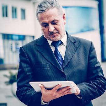 Erfolgreicher geschäftsmann mit digitalem tablet auf dem hintergrund des büros