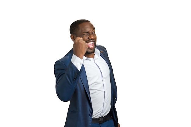 Erfolgreicher geschäftsmann mit erhobener faust. fröhlicher schwarzer mann in abendgarderobe hob die faust als champion