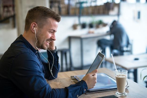 Erfolgreicher geschäftsmann mit kopfhörern, die tablette in café-bar verwenden