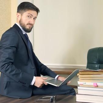 Erfolgreicher geschäftsmann sitzt am bürotisch und arbeitet mit laptop