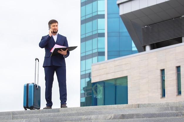 Erfolgreicher geschäftsmann steht mit dokumenten in den händen auf den stufen gegen das bürogebäude
