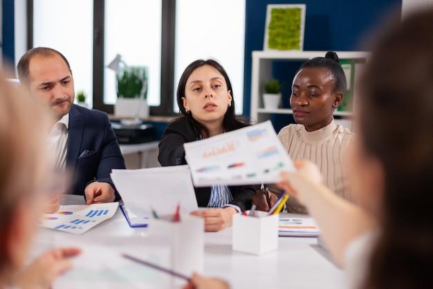 Erfolgreicher geschäftsmann und mitarbeiter, die im konferenzraum über dokumente diskutieren