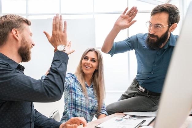 Erfolgreicher geschäftsmann und seine kollegen am arbeitsplatz im büro. das konzept der teamarbeit