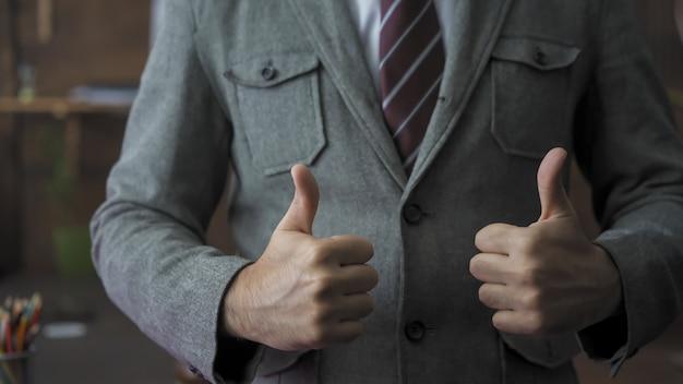 Erfolgreicher geschäftsmann zeigt eine daumen hoch geste. der männliche anführer drückt positive emotionen aus, um sein team aufzuheitern. erfolgreiches geschäftskonzept