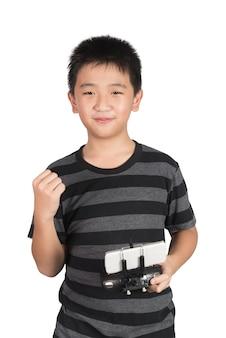 Erfolgreicher glücklicher asiatischer junge, der funkfernbedienung für brummen hält