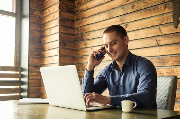 Erfolgreicher glücklicher geschäftsmann, der auf einem mobile spricht