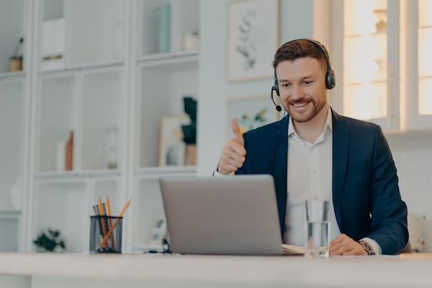 Erfolgreicher, glücklicher geschäftsmann im anzug, der den daumen hochhält und den laptop-bildschirm mit einem lächeln betrachtet, während er online mit kollegen kommuniziert und von zu hause aus arbeitet. fernes arbeitsplatzkonzept
