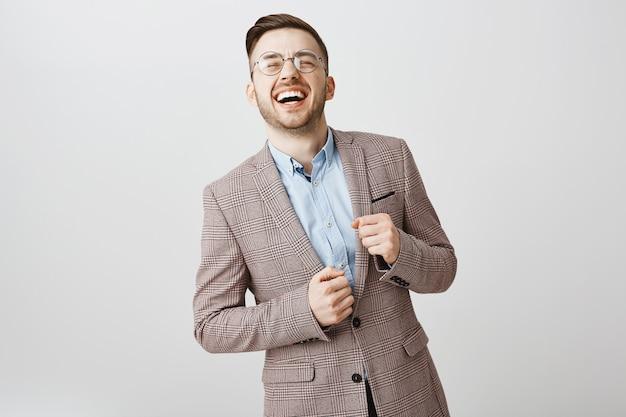 Erfolgreicher glücklicher geschäftsmann im anzug, der laut lacht