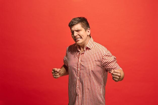Erfolgreicher glücklicher mann, der feiert, ein gewinner zu sein. dynamisches bild des kaukasischen männlichen modells auf rotem studiohintergrund.