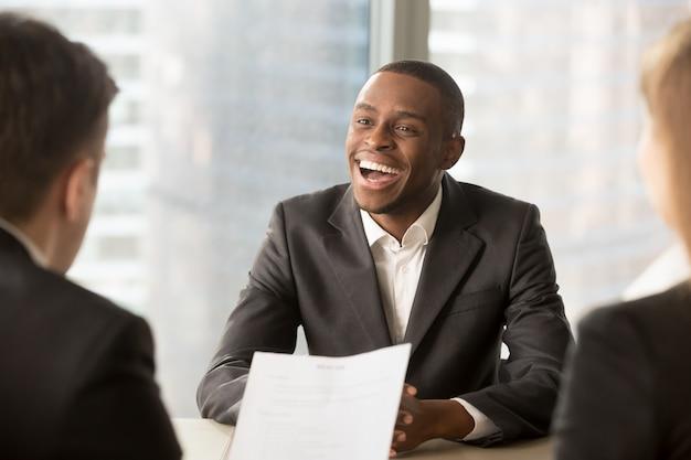 Erfolgreicher glücklicher schwarzer männlicher kandidat, der eingestellt wurde, bekam einen job