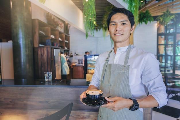 Erfolgreicher hübscher geschäftseigentümer, der mit einem tasse kaffee vor bar steht