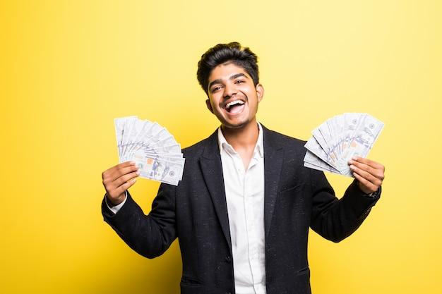 Erfolgreicher indischer unternehmer mit dollar-banknoten im klassischen anzug der hand, der kamera mit zahnigem lächeln betrachtet, während er gegen gelbe wand steht