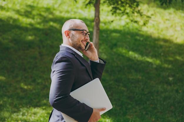 Erfolgreicher intelligenter geschäftsmann in weißem hemd, klassischem anzug, brille. mann steht mit laptop-pc-computer, telefoniert mit handy im stadtpark draußen auf naturhintergrund. seitenansicht, geschäftskonzept.