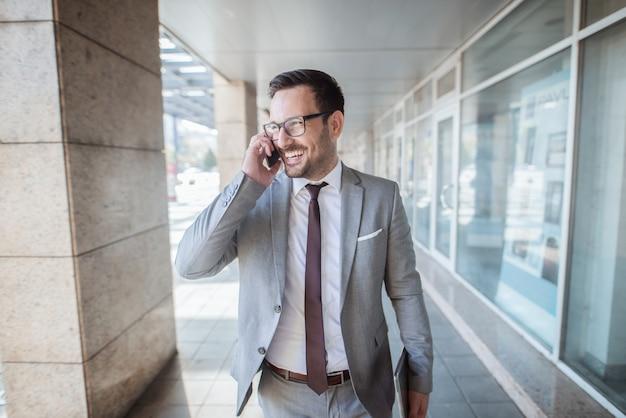 Erfolgreicher junger angestellter, der smartphone für geschäftsgespräche verwendet, während er vor geschäftszentrum steht. in der anderen hand tablette.