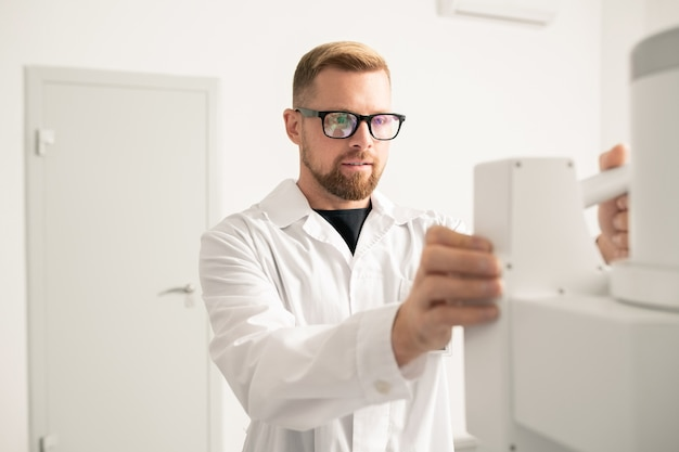 Erfolgreicher junger arzt in weißmantel und brille, der vor modernen medizinischen geräten steht, während er in kliniken arbeitet