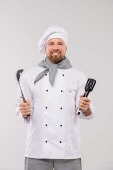 Erfolgreicher junger bärtiger koch in der uniform, die küchengeschirr hält, während sie isoliert mit lächeln betrachten