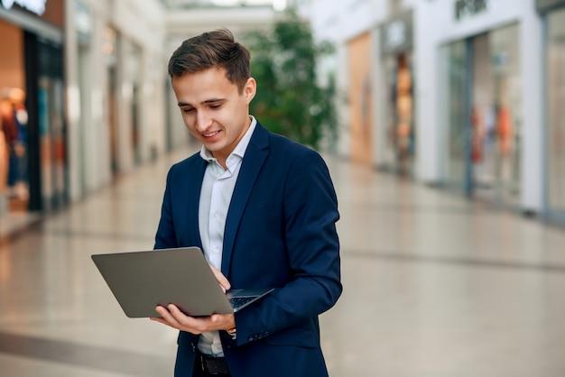 Erfolgreicher junger geschäftsmann, der am laptop arbeitet
