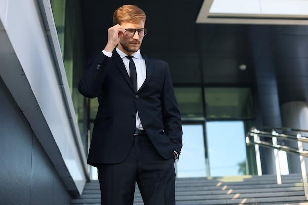 Erfolgreicher junger geschäftsmann, der die hand auf der brille hält, während er die treppe vor dem bürogebäude hinuntergeht.