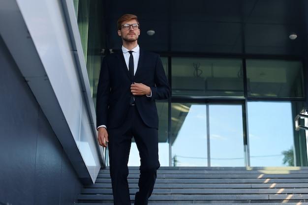 Erfolgreicher junger geschäftsmann, der die treppe außerhalb des bürogebäudes hinuntergeht.