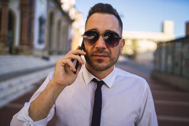 Erfolgreicher junger geschäftsmann in einem formellen outfit mit sonnenbrille, die am telefon spricht