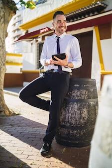 Erfolgreicher junger geschäftsmann in einem formellen outfit unter verwendung einer tablette