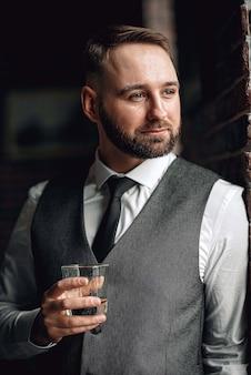 Erfolgreicher junger geschäftsmann in weste und krawatte. mit einem stilvollen und stilvollen haarschnitt und bart. er hielt ein glas whisky in den händen