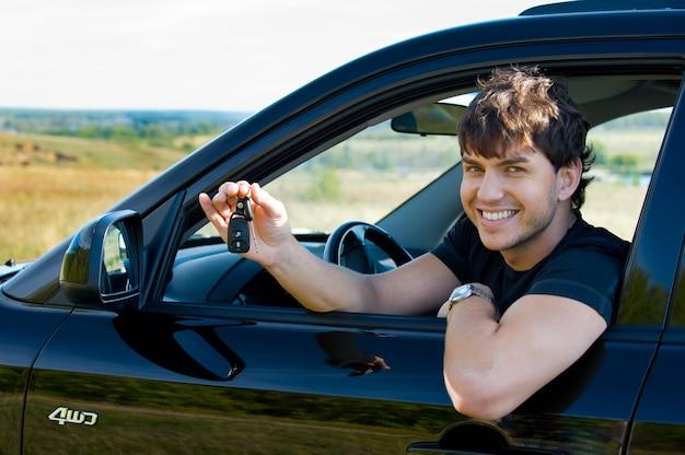 Erfolgreicher junger glücklicher mann, der die schlüssel zeigt, die im neuen auto sitzen