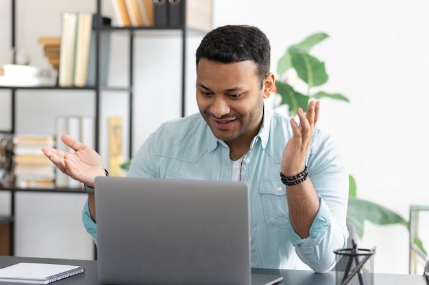Erfolgreicher junger indischer geschäftsmann, der laptop für die videokommunikation mit mitarbeitern verwendet. videokonferenz- oder online-bildungskonzept