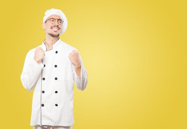 Erfolgreicher junger koch, der eine wettbewerbsfähige geste tut
