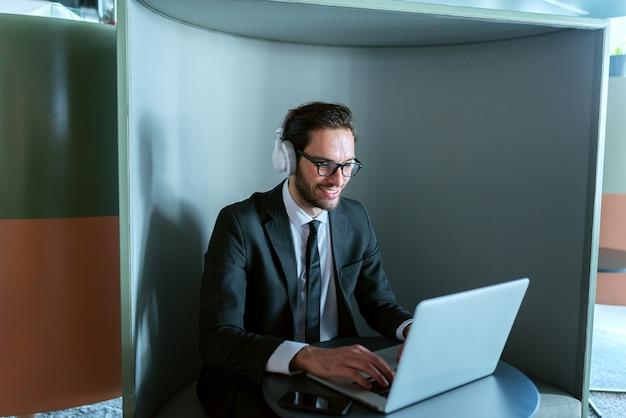 Erfolgreicher junger manager, der telefonkonferenz hat und in seiner arbeitsstation sitzt. kopfhörer an den ohren.