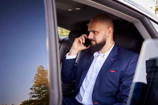Erfolgreicher junger mann, der am telefon in einem auto spricht.