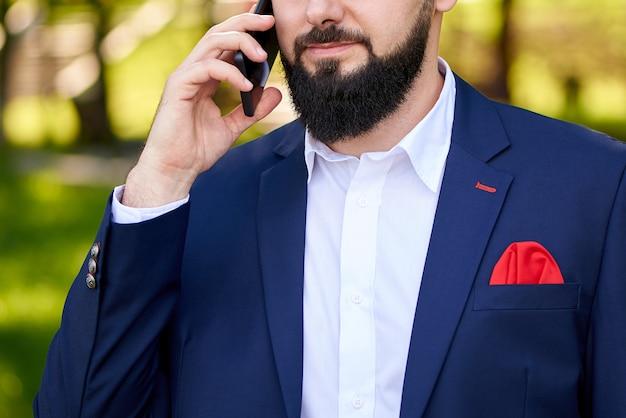 Erfolgreicher junger mann, der am telefon spricht.